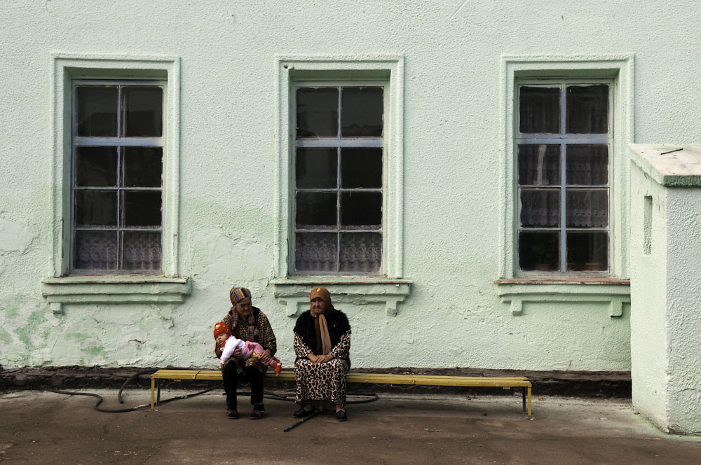 Ethnic Uzbek women wait for relatives outside a polling station after having cast their ballots.