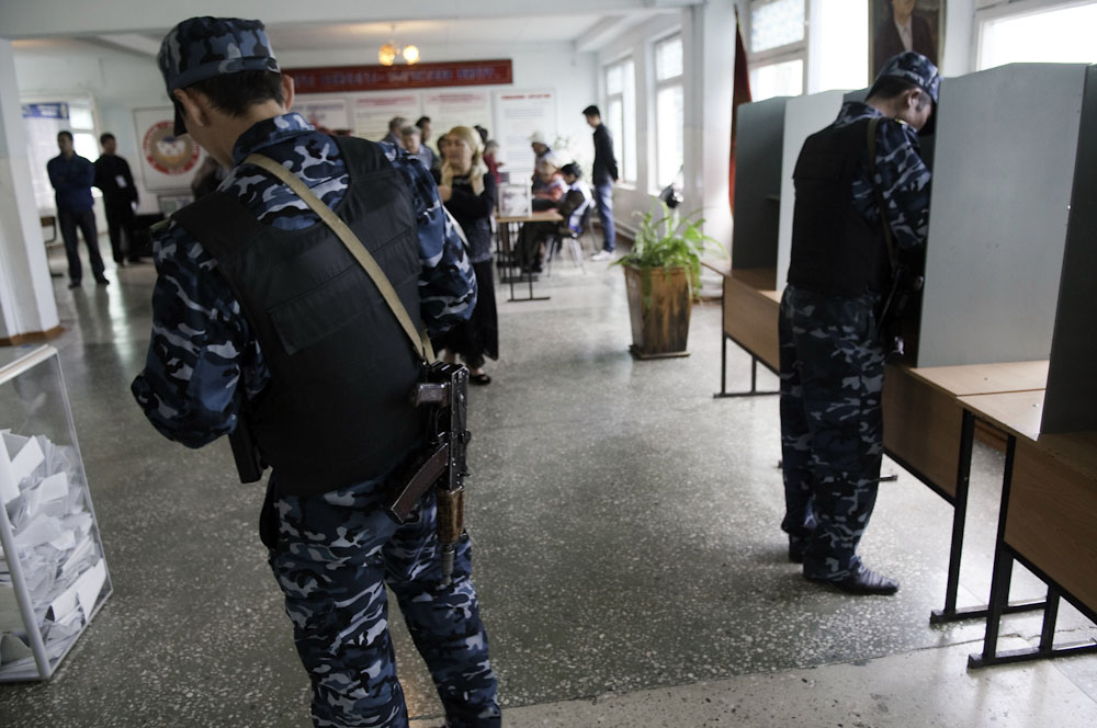 Armed security guards vote at a polling station in the Yuri Gagarin primary school.