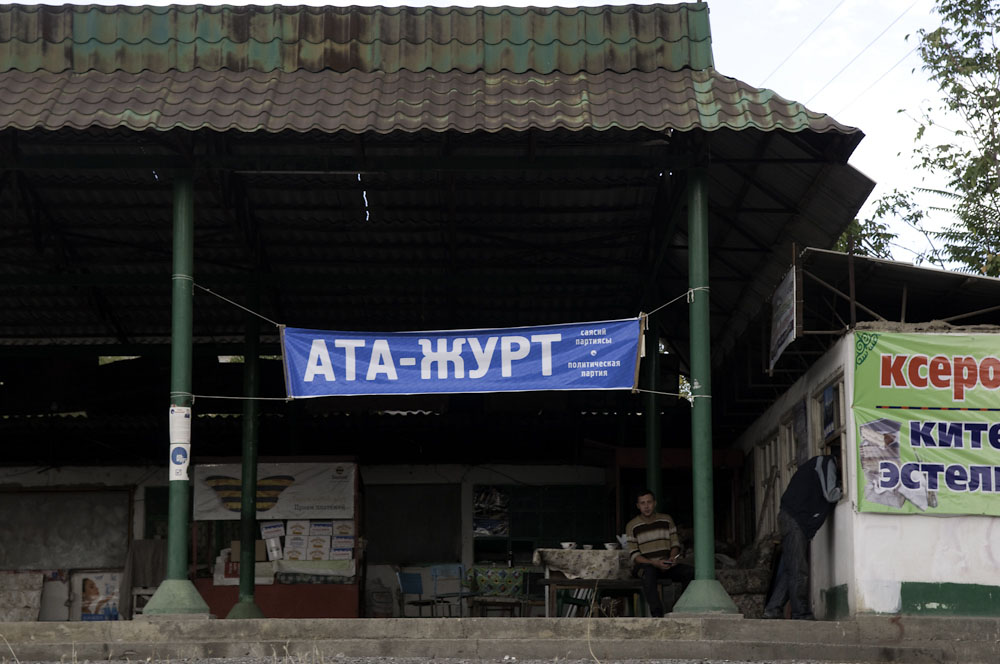 A man sits in a cafe under a campaign banner for the Ata-Jurt party.