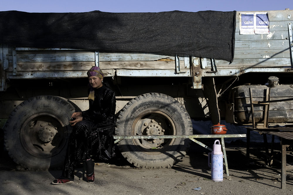 A young ethnic Uzbek woman rests near an unused truck pasted with signs of political parties.