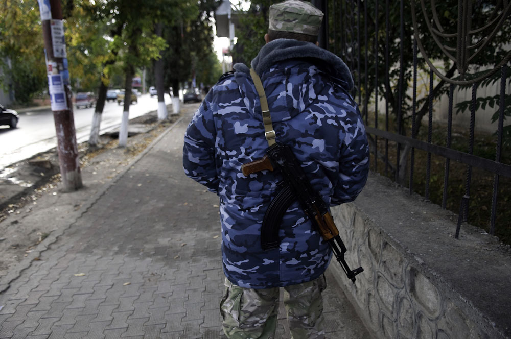 An armed security guard carries a Kalishnikov on the streets of Osh.