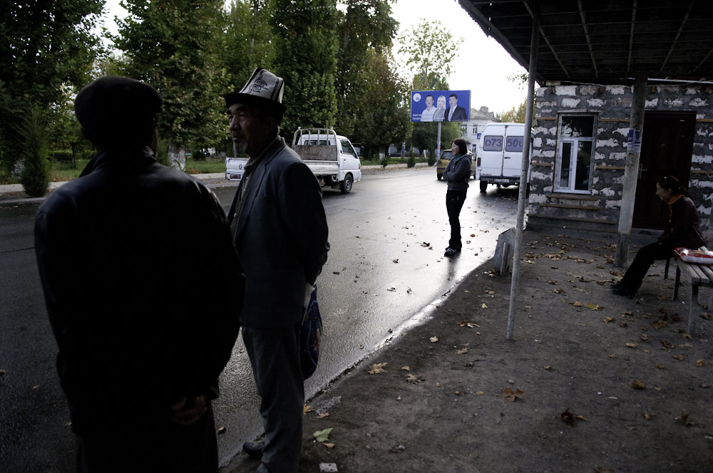 An ethnic Kyrgyz man and other passengers wait for a bus near a campaign billboard for the Ata-Jurt party.