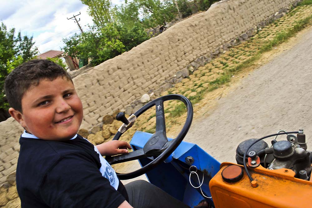 A boy happily drives a paht-paht along a village road.