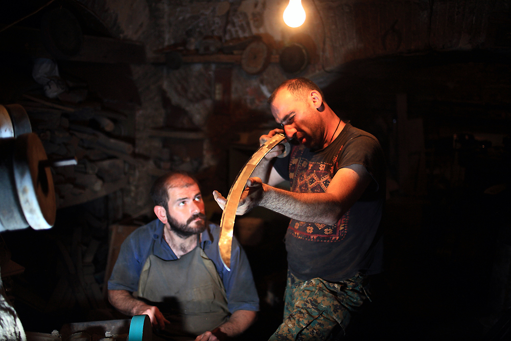 Giga Gorgiashvili watches Zakro Nonikashvili evaluating the sharpness of a sword blade in Georgia. (Temo Bardzimashvili)