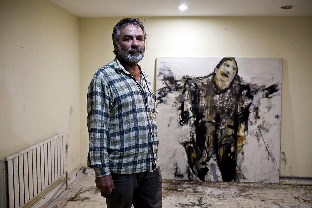"Prominent Turkish artist Ali Kotan stands near a painting from his new ""white series"" in his Ankara gallery. (Justin Vela)"