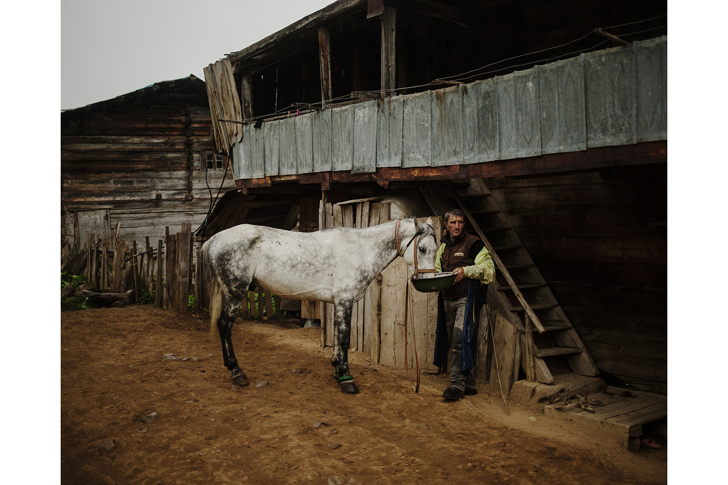 A man feeds his horse in Zotikeli