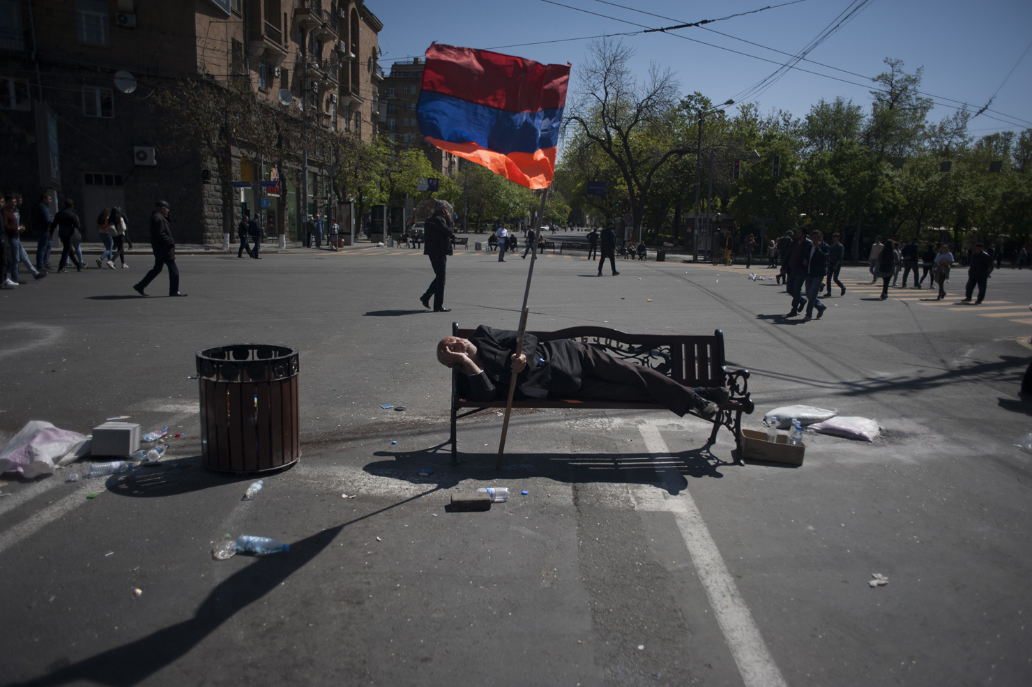 An man rests on a bench while holding the Armenian flag, April 17