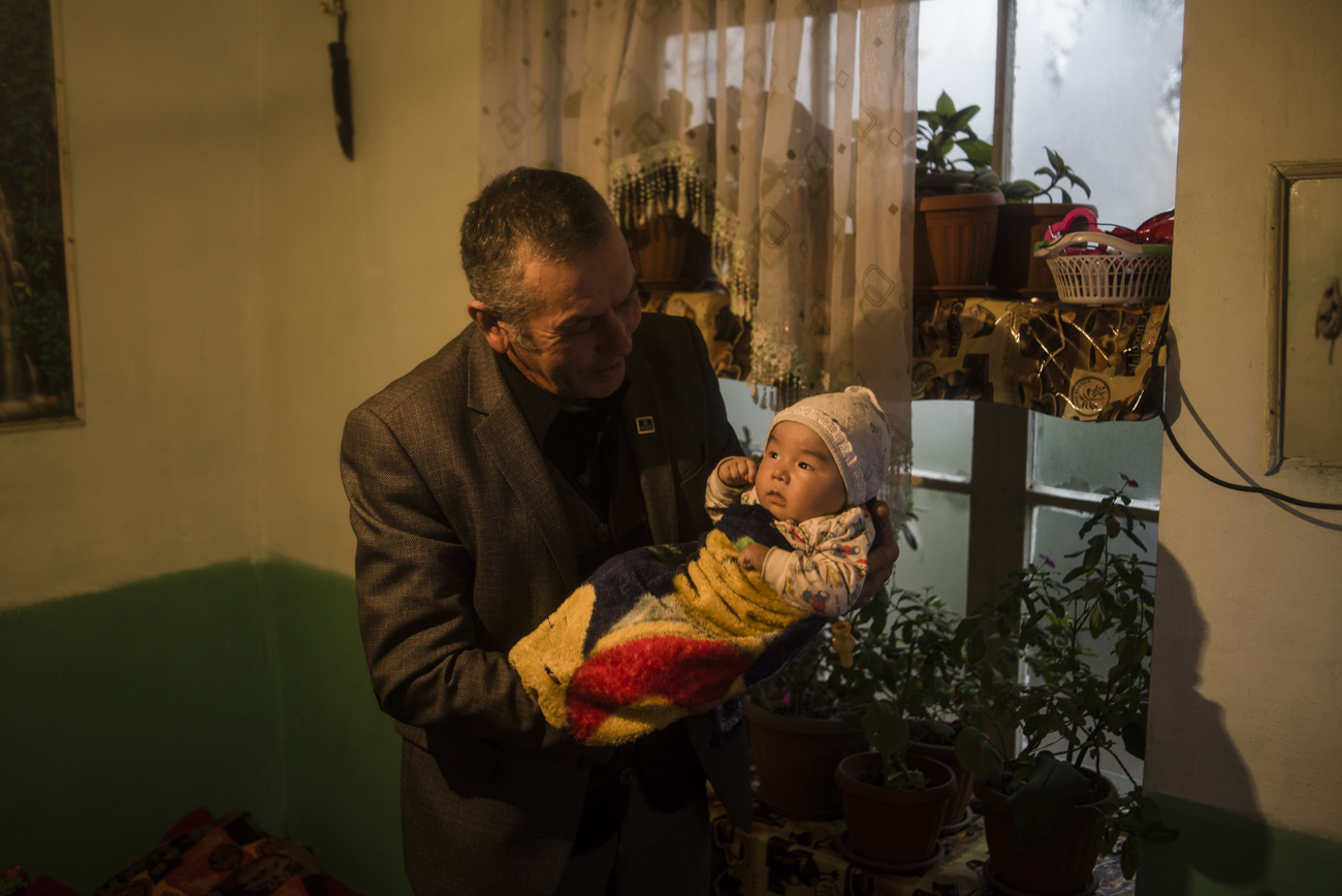 Sulaimanov Kurmanbek with his younger grandson at home in the village of Ayuu