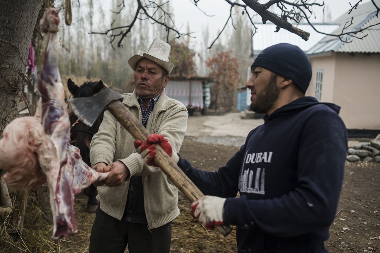 Sulaimanov Kurmanbek and his son Kahramon carve a ram for the feast in honor of the circumcision of his grandson Otabek in the village of Ayuu.