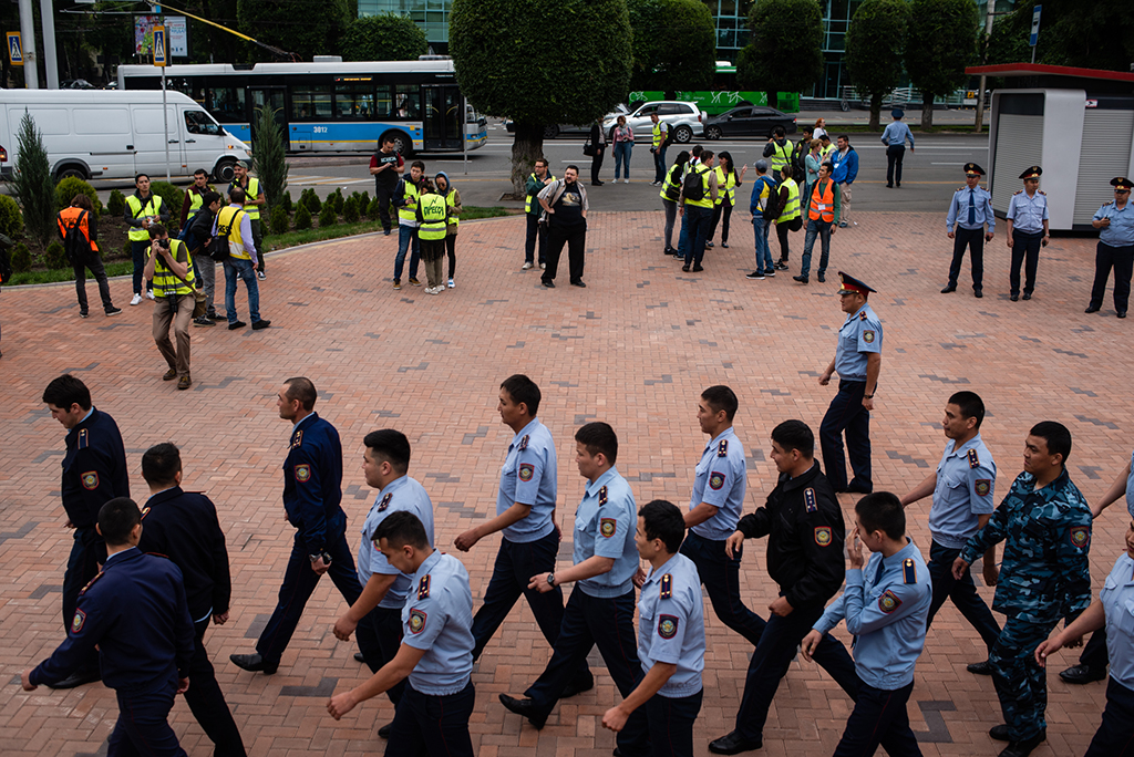 Police and journalists prepare for a rally that had been called near the Baluan Sholak sports center in Almaty.