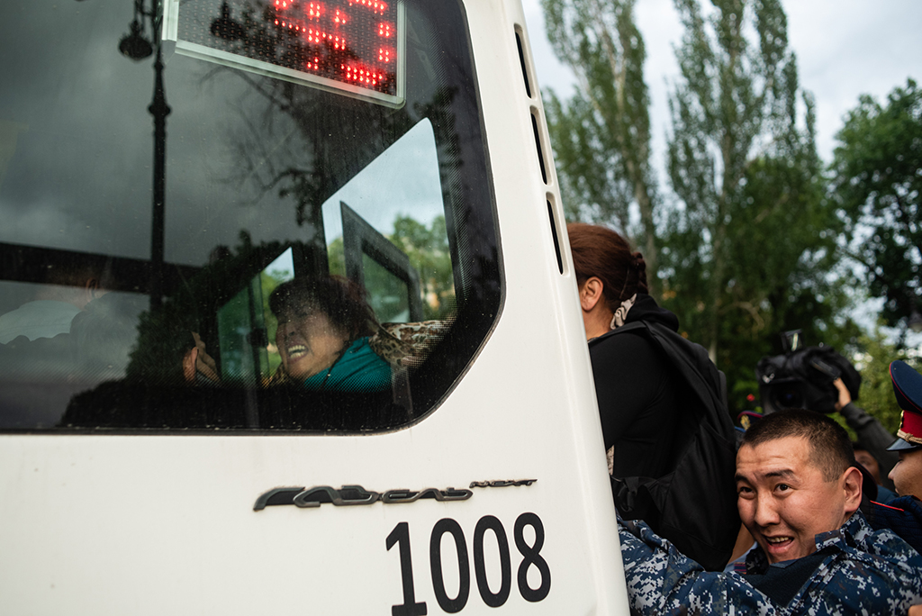 Police push detainees onto a bus in Almaty's old square.