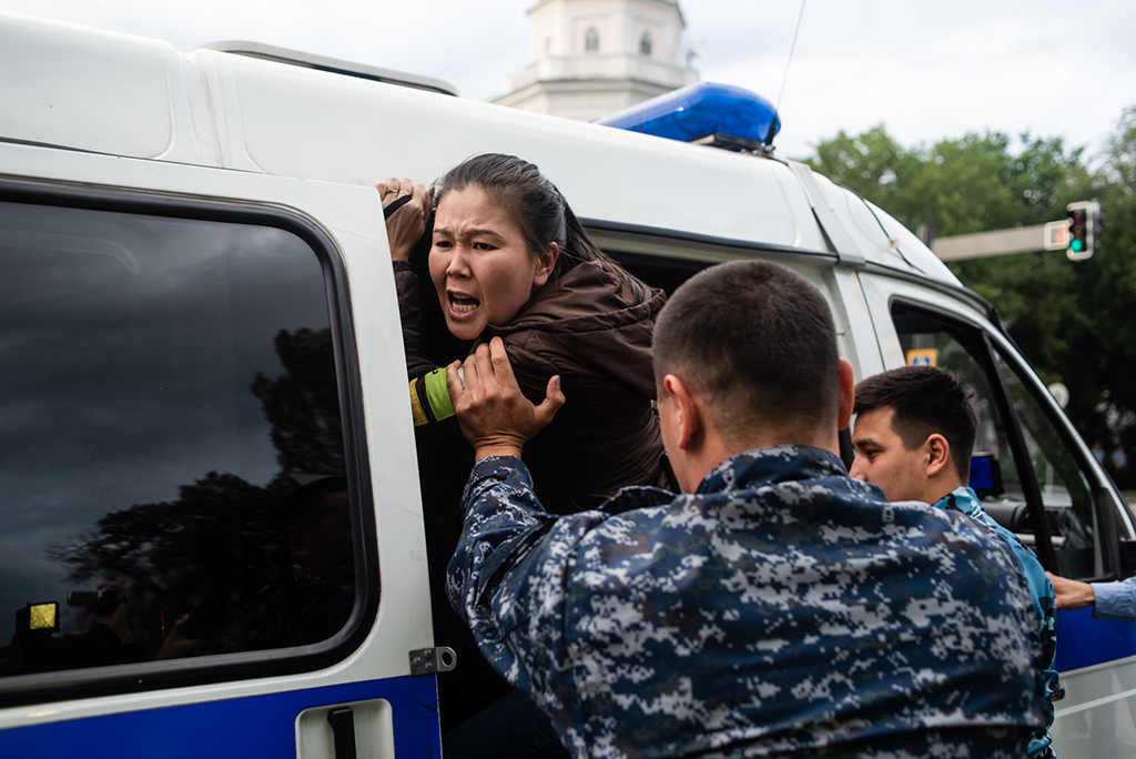 A detainee refuses to sit in a police paddy wagon in Almaty's old square.