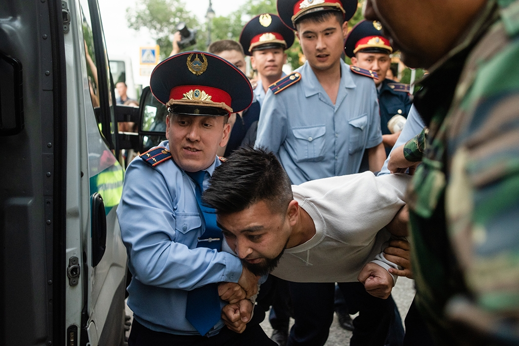 Dimash Alzhanov being pushed into a paddy wagon on June 12. (photo: Danil Usmanov)