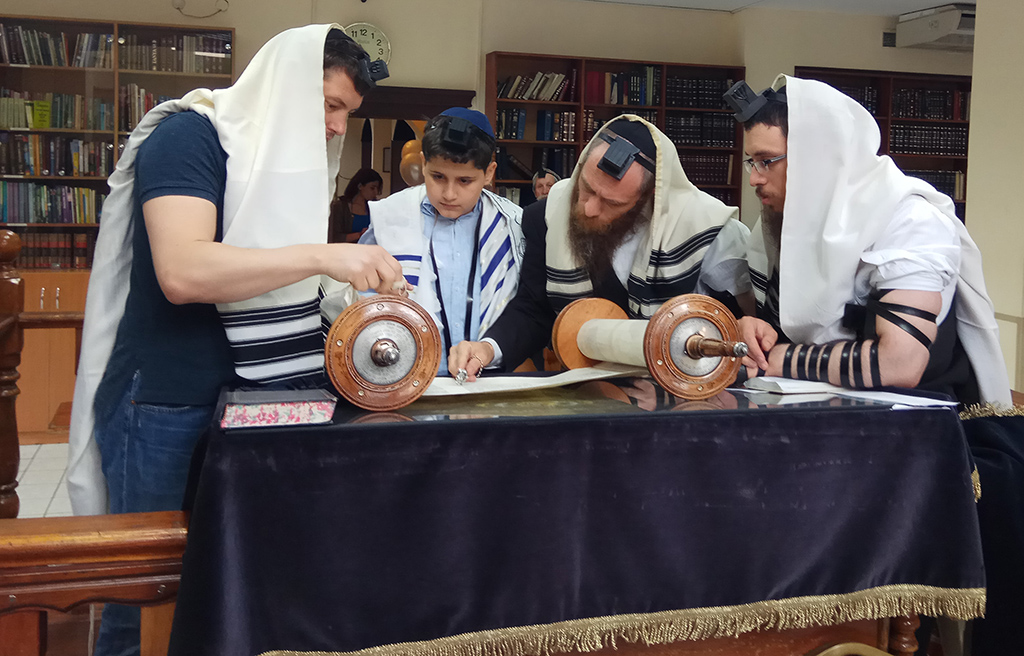 At his bar mitzvah a boy reads from the Torah accompanied by Rabbi Elchanan Cohen, Almaty's chief rabbi.