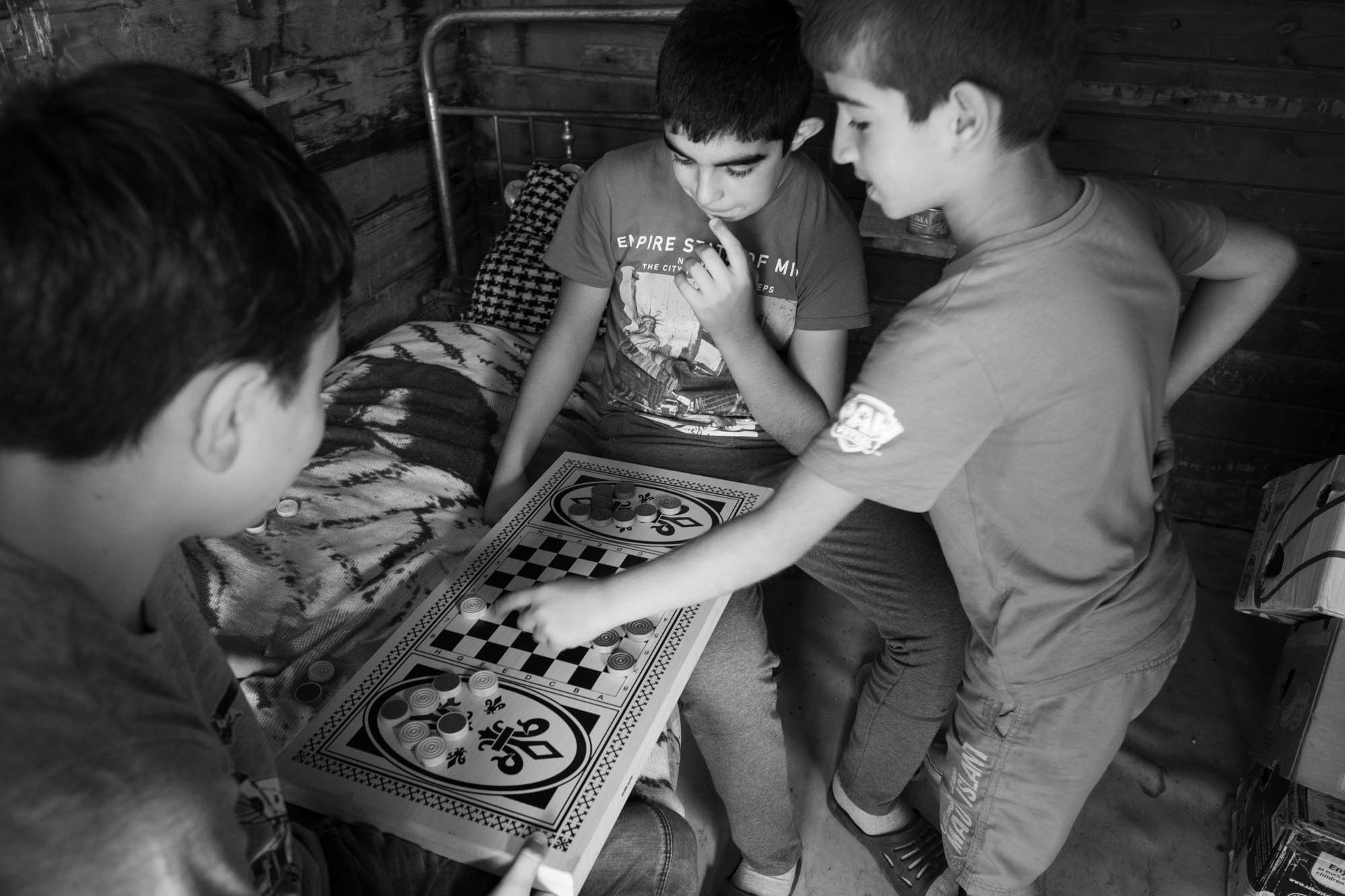 پسران اهل قره باغ در حالی که مادرانشان بیرون از باغ سیب در باغی نزدیک ایروان کار می کنند ، چکر بازی می کنند.  (عکس: وینسلو مارتین)