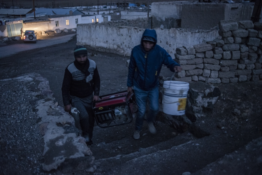 Two men carrying a power generators in Murghab