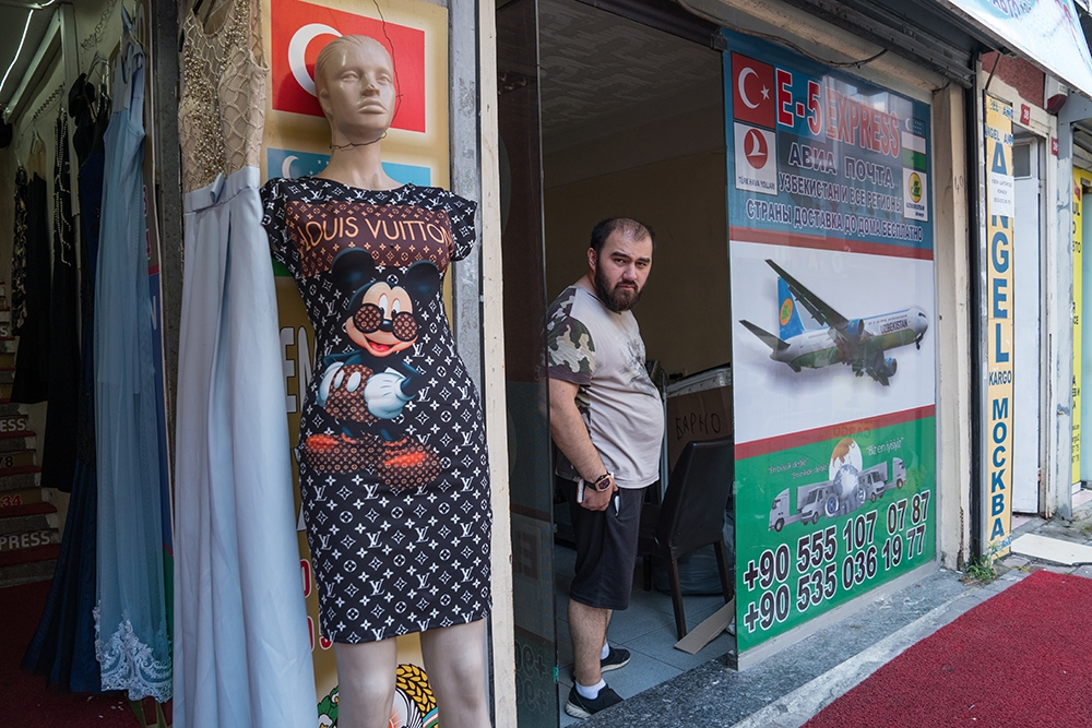 A man stands by his cargo shop, which specializes in transport to Uzbekistan.