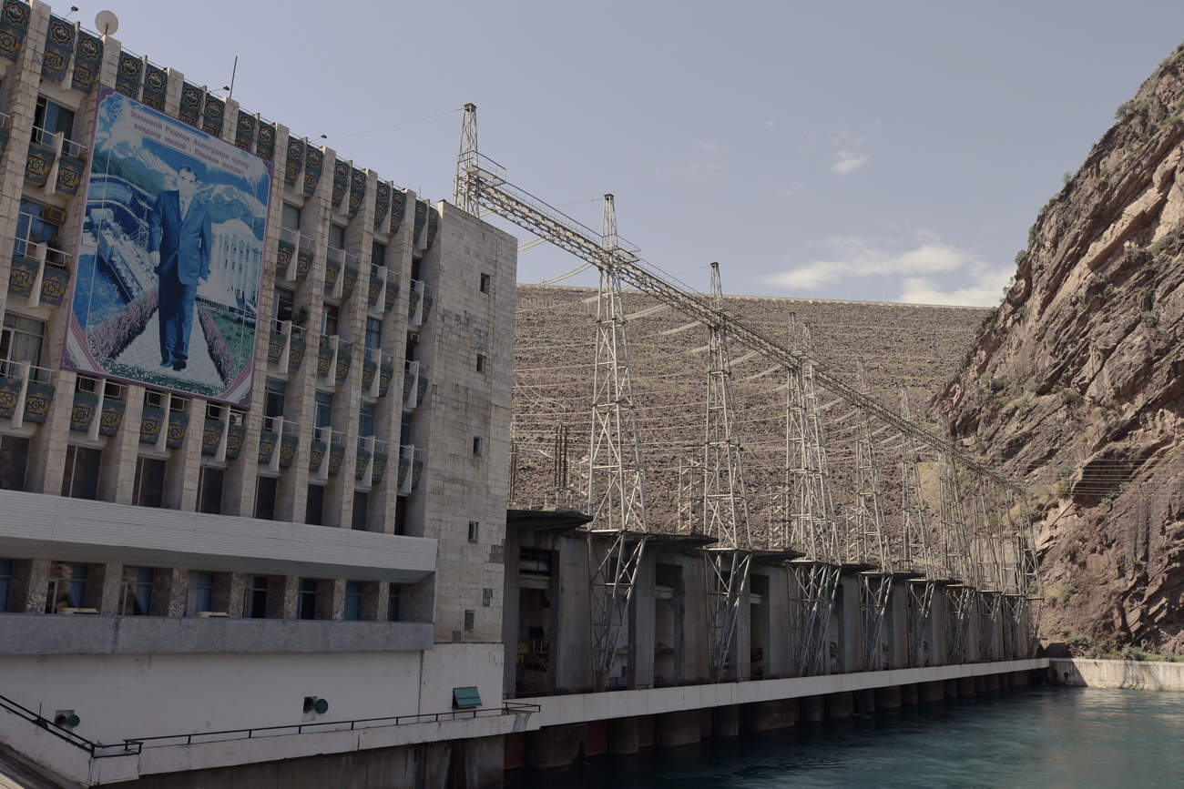 Exterior view of the production unit at the Nurek hydroelectric dam featuring a faded poster of President Emomali Rahmon.