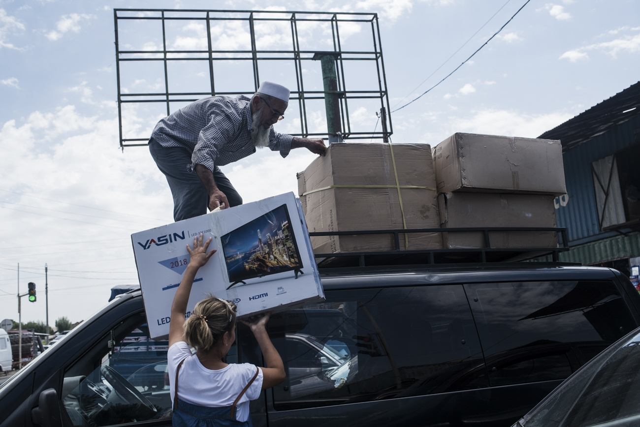 A taxi driver loads household appliances