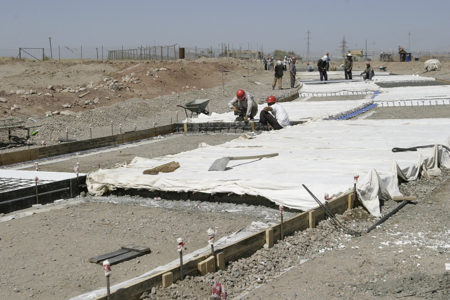 Workers on the Tajik side lay down the final stretch of road to meet the new bridge. (David Trilling for EurasiaNet)