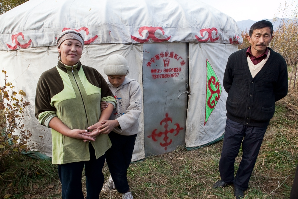 Anara Bolotova with her husband Marat Moldokanov and son in front of a Chinese yurt they imported. The yurt has a metal door and takes only 20 minutes to assemble, Bolotova says.