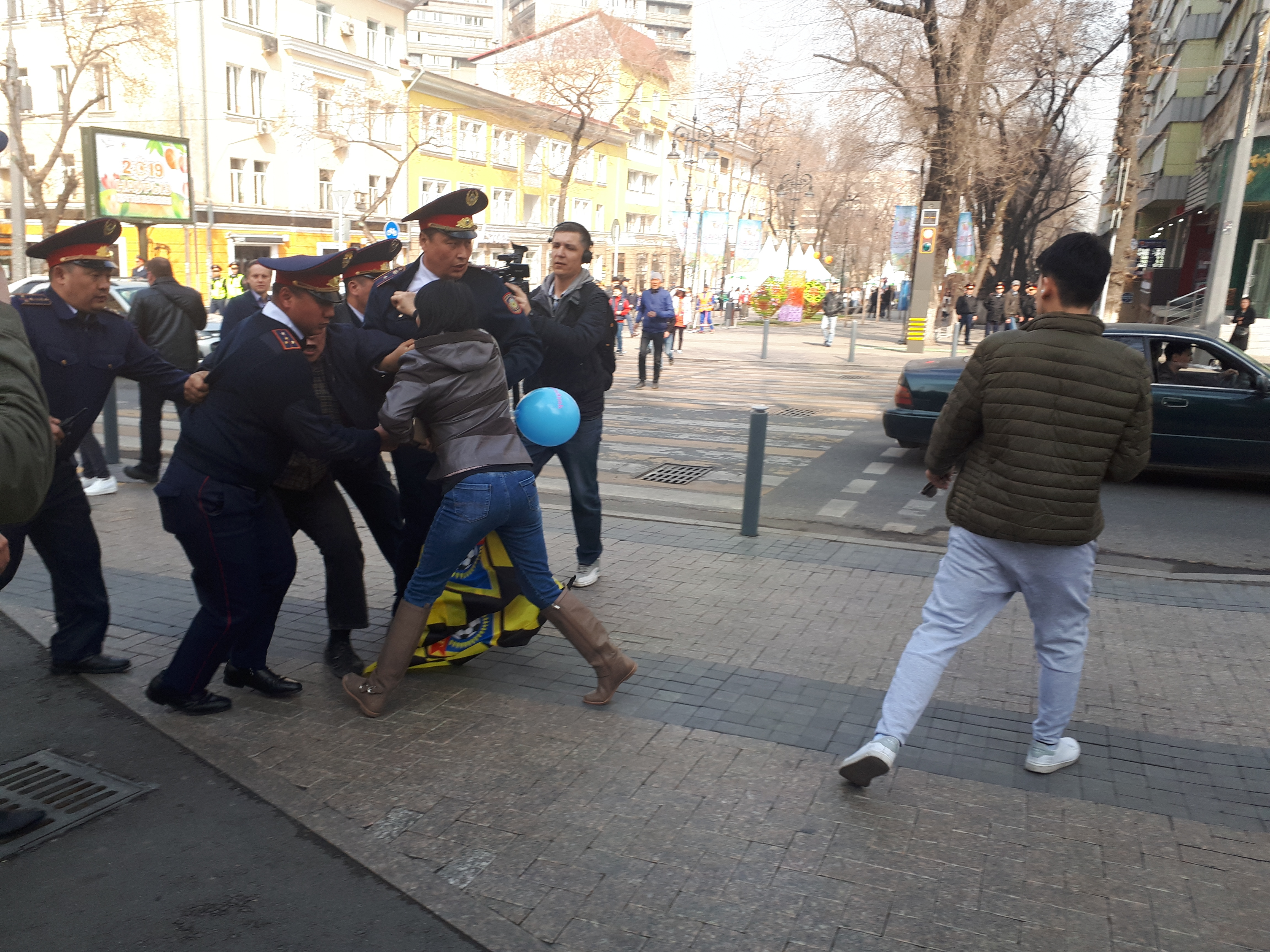 It's raining policemen: A female demonstrator and her blue balloon are dragged away from a demo in downtown Almaty. (Photo: Joanna Lillis)