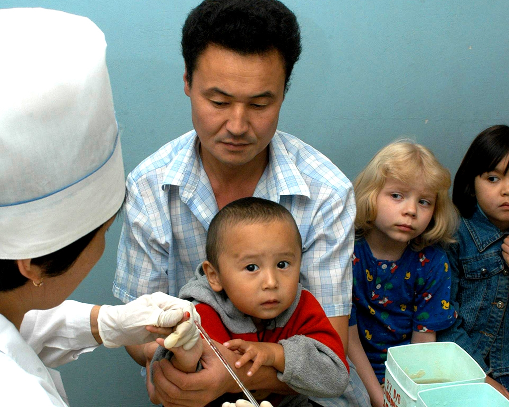 A health worker in Kazakhstan collects blood samples from children