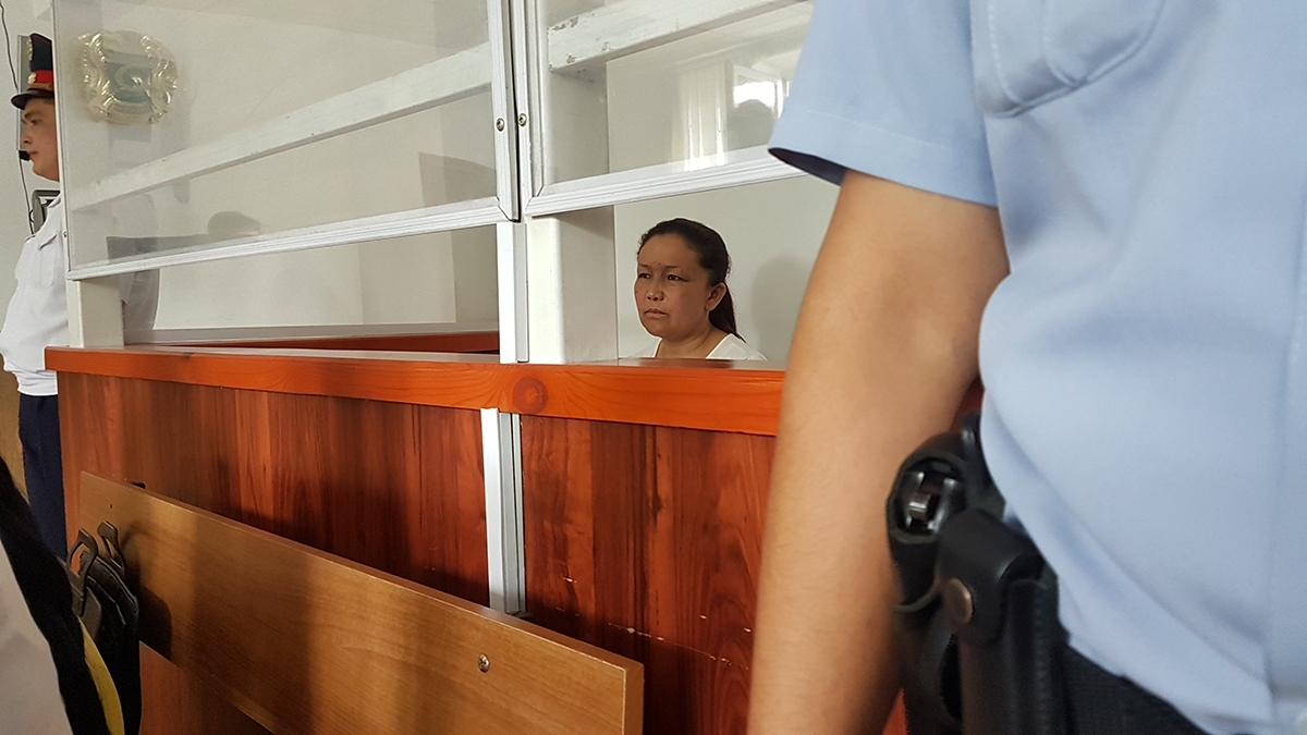 Sayragul Sauytbay, an ethnic Kazakh and Chinese citizen, sits enclosed in the glass cage reserved for defendants at her trial in Zharkent in 2018. (Photo: Almaz Kumenov)