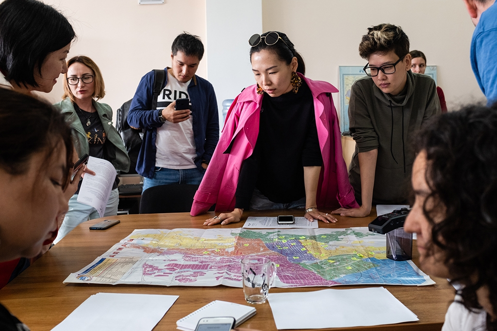 Independent observers study a map of polling stations in Almaty the day before the election. (Danil Usmanov)