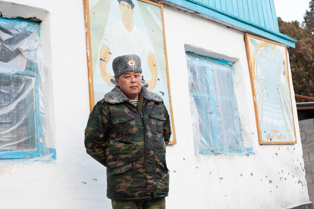 Kyrgyz Col. Erzat Shamshiev stands before a wall that took Kalashnikov fire during the shootout at Glavny.