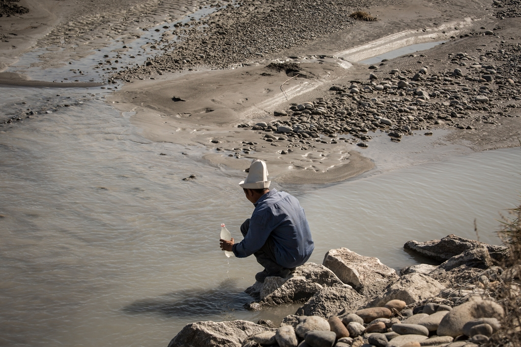 Jusubali Jamylbaev, 48, a shepherd, fills a bottle with water from River Soh in Aktoprak, Kyrgyzstan.