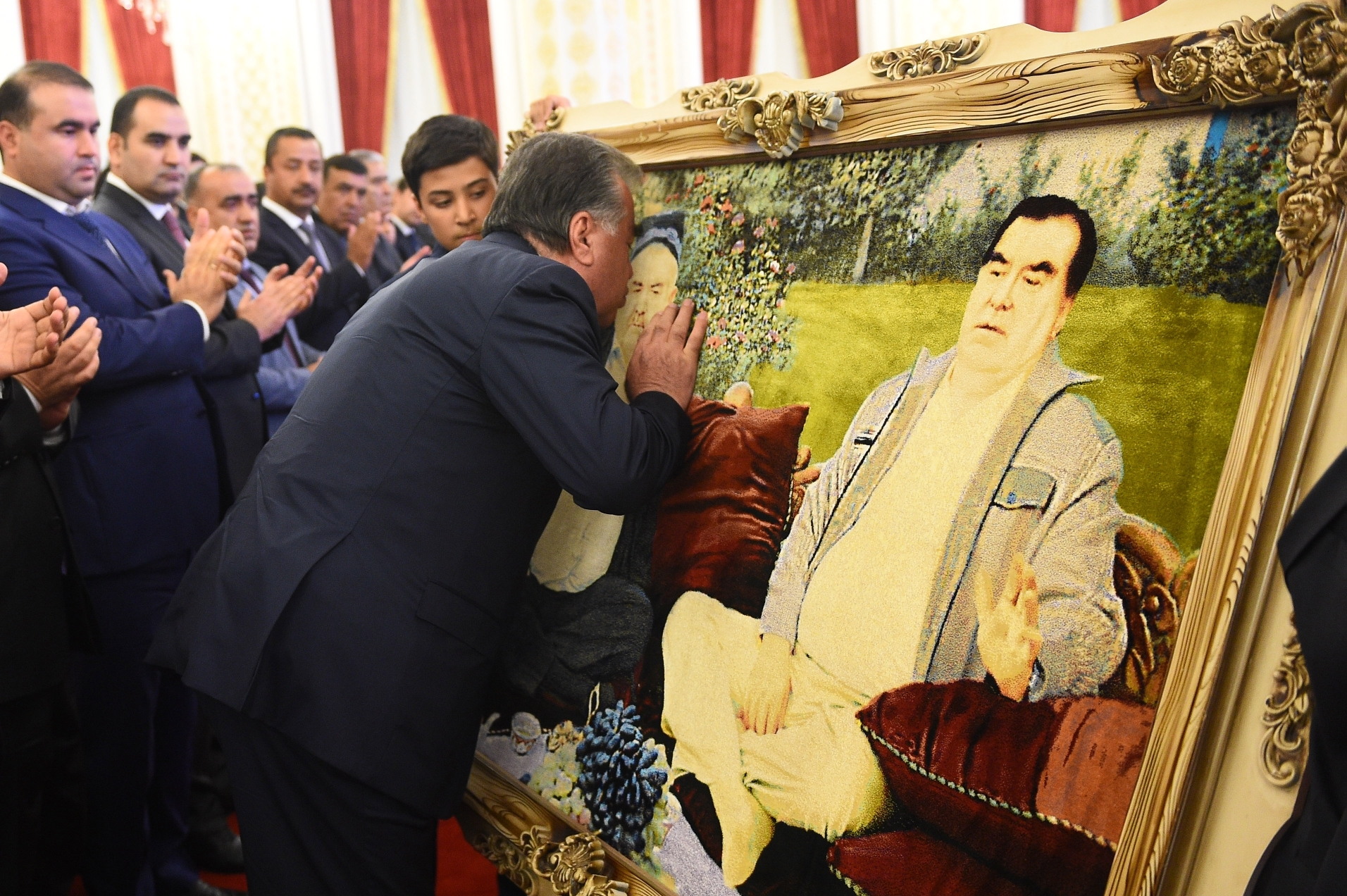 Carpet comforts: President Rahmon kissing a portrait of his late brother and himself that was produced by carpet-weavers. Sohibov can be seen in this photo at far left. (Photo: Presidential administration)