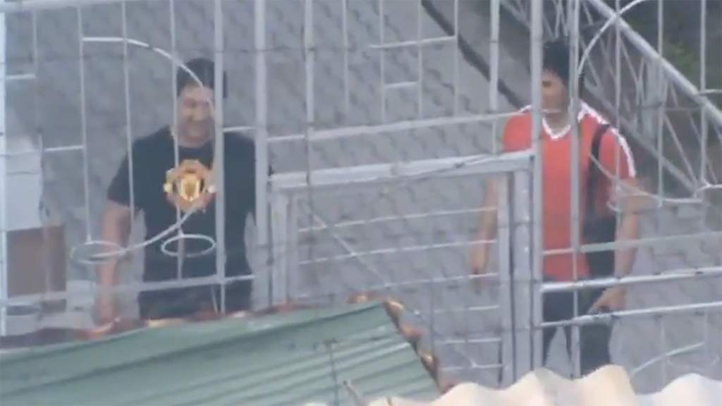 Dosonov, left, seen leading Sarkarbayev to the gates of a jail in Osh in 2015. (Photo: Facebook video screengrab)