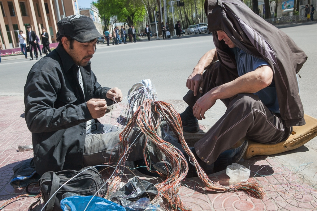 Workers untangle communication cables in downtown Dushanbe