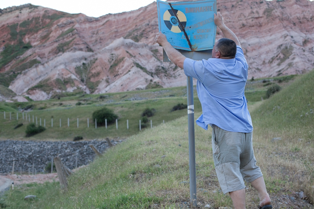 An official with Kyrgyzstan's Ministry of Emergency Situations fixes a rusting sign warning locals to stay off the tailings dumpsite. (Photo: David Trilling)
