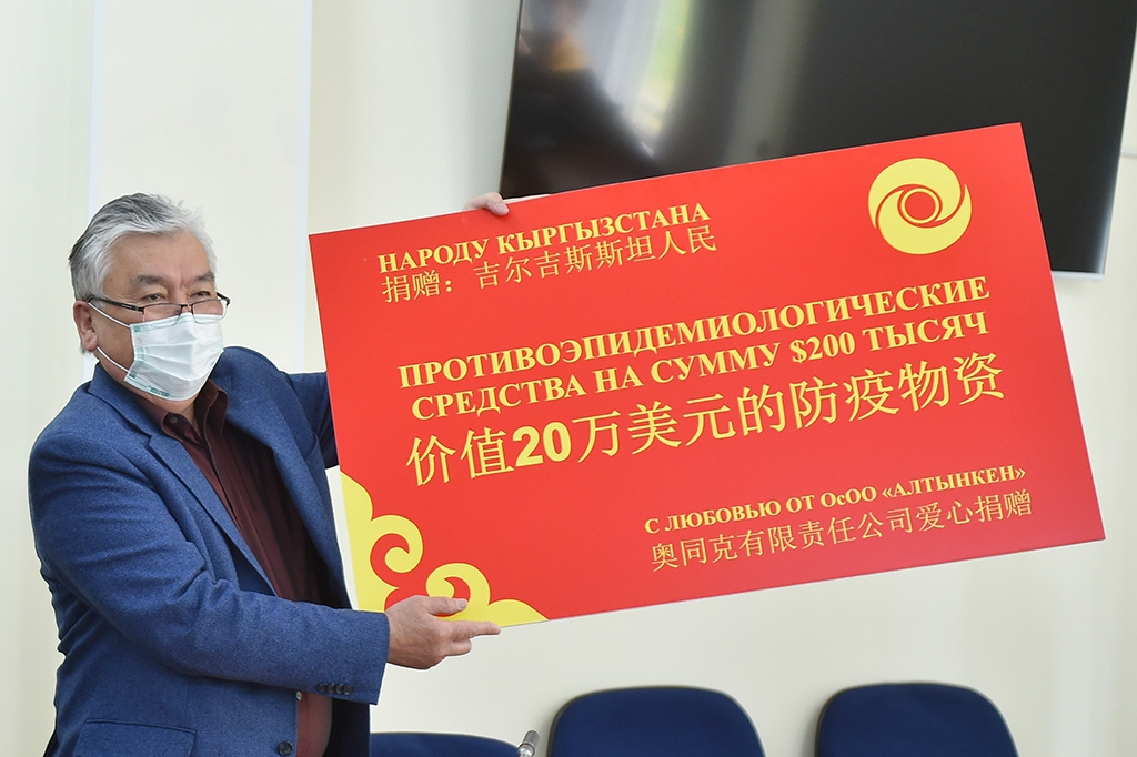 "We have a winner: Kyrgyz Health Minister Sabirjan Abdikarimov receiving $200,000 worth of aid ""with love from Altynken LLC,"" a Chinese mining firm. (gov.kg)"