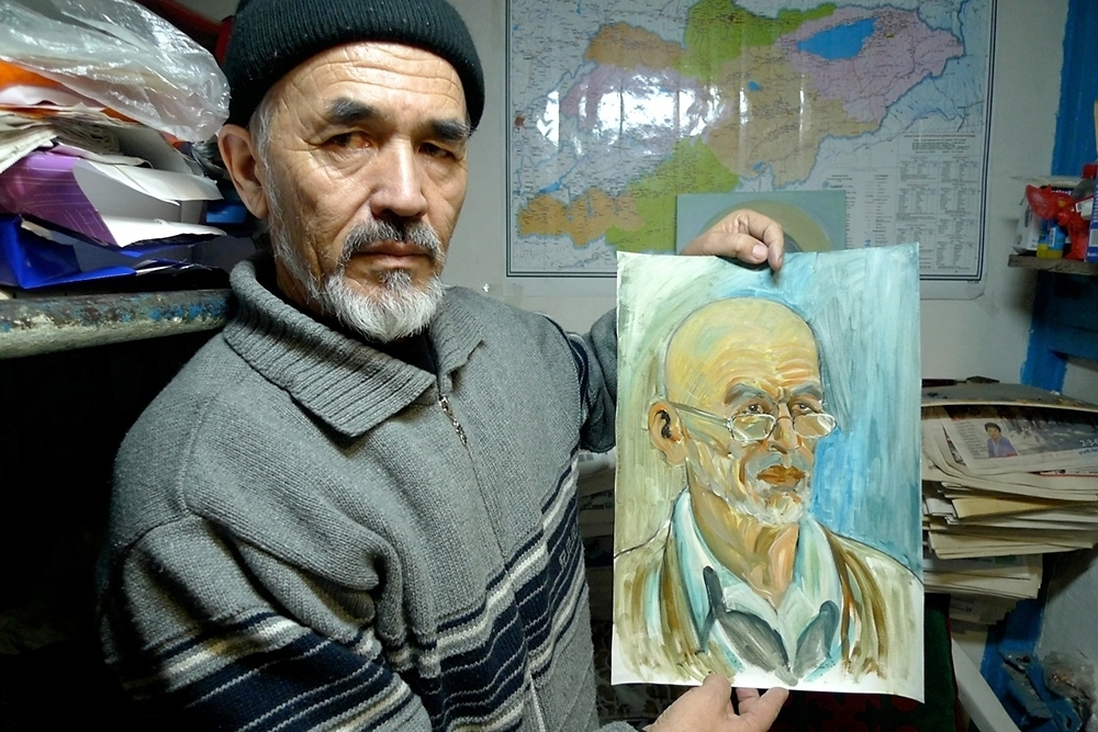 Rights activist Azimjan Askarov, seen here holding one of his self-portraits in his basement prison cell in February 2012. (Photo: Nate Schenkkan)