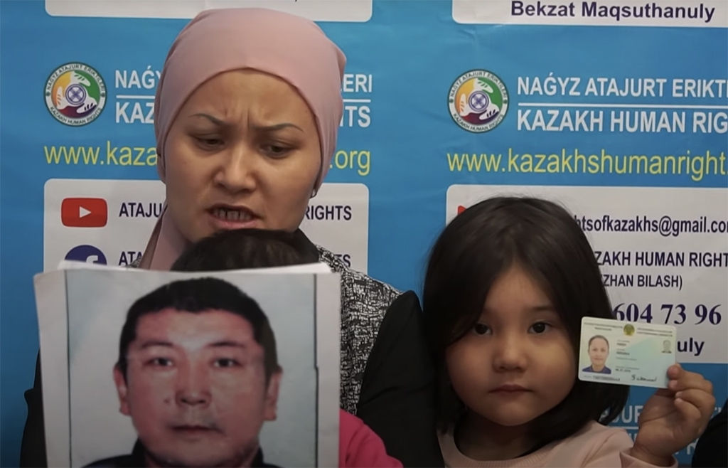 Bikamal Kaken and her daughter hold up a picture of Adilgazy Muqai while recording a statement in Almaty. (Atajurt)
