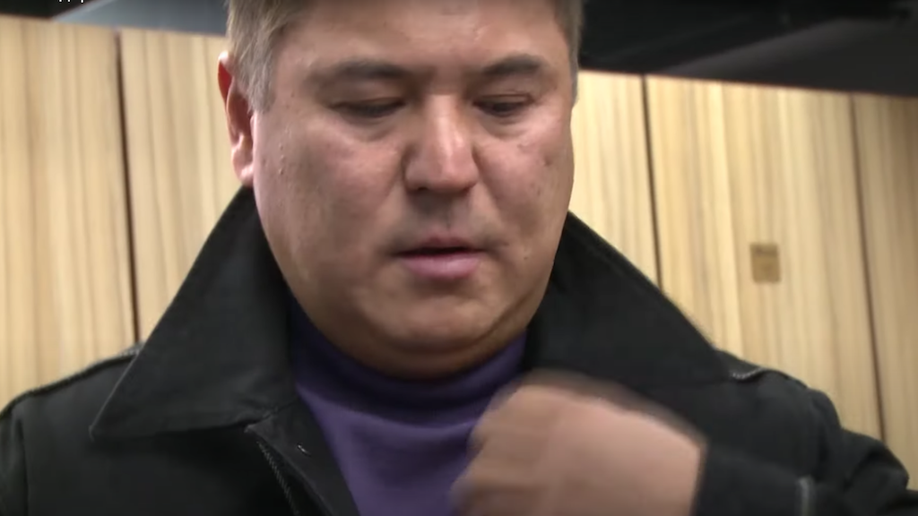 Looking good: Kolbayev straightens his collar before being placed in handcuffs. (Photo: GKNB video screengrab)