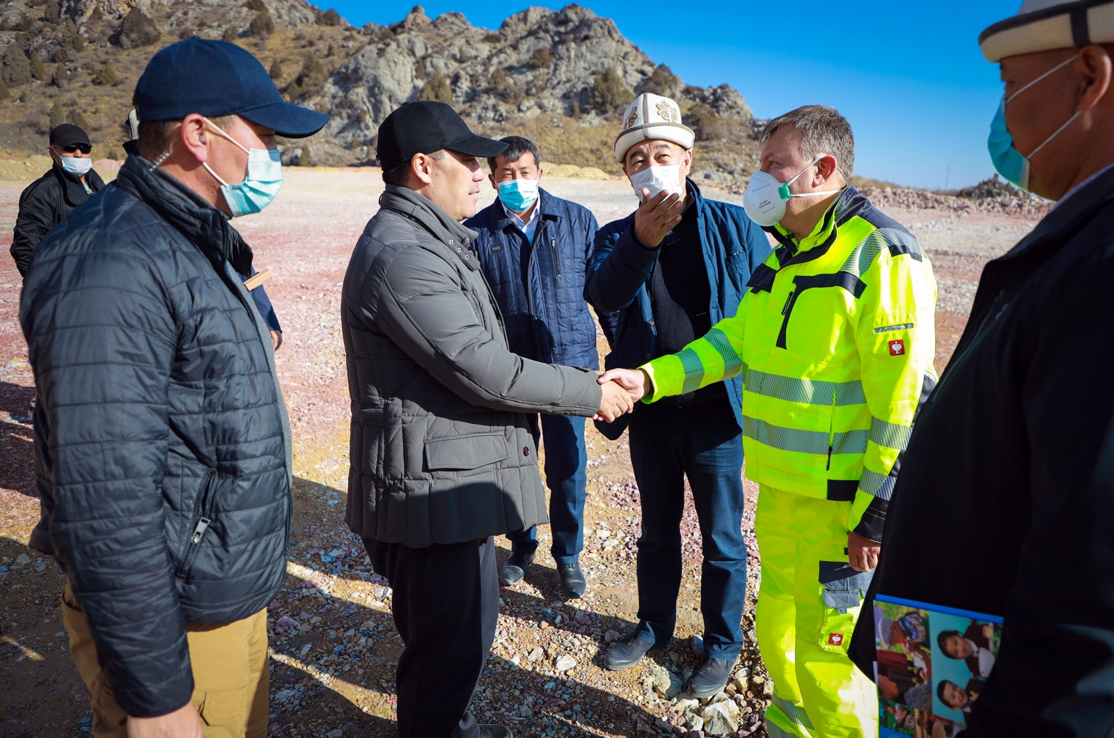 Japarov, center, shaking hands with a representative from the company developing the Bozymchak mine. (Photo: Government website)