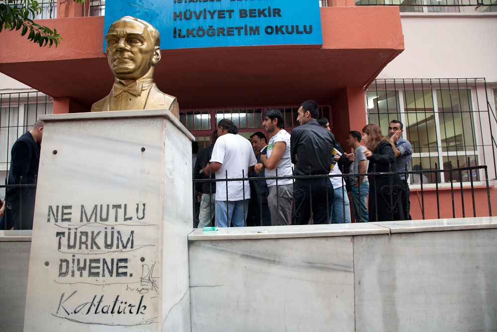 Behind a bust of Mustafa Kemal Ataturk, voters gather at a polling station in Istanbul. (Photo: Jonathan Lewis)