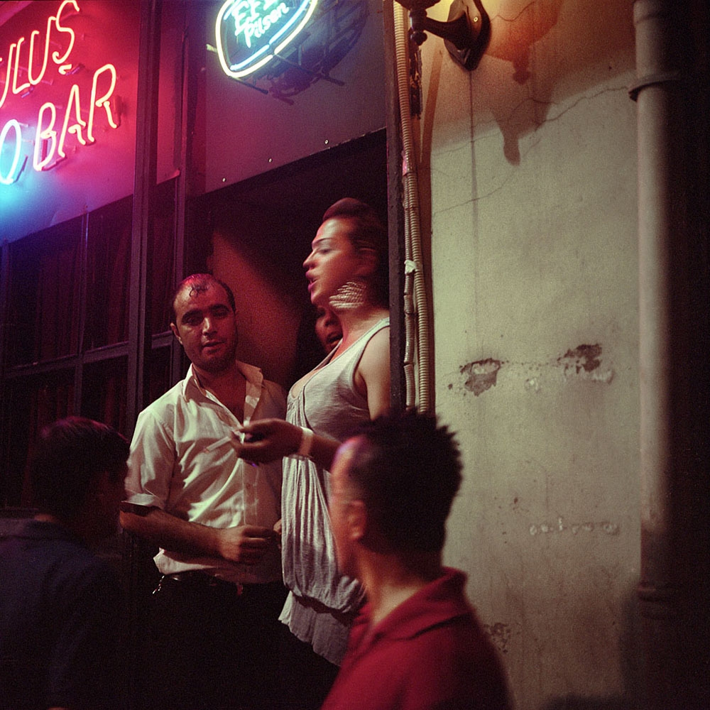 A transgender sexworker stands in the doorway of an Istanbul bar, where she works at night.