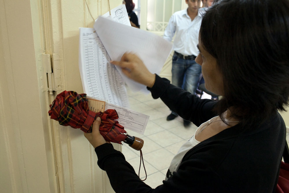 A voter searches a list of names to make sure she can cast her ballot at the correct polling station. (Photo: Jonathan Lewis)