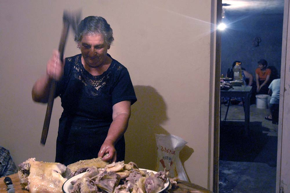 A woman cuts chicken with an axe as she prepares traditional dishes for a wedding supra in Supsa.