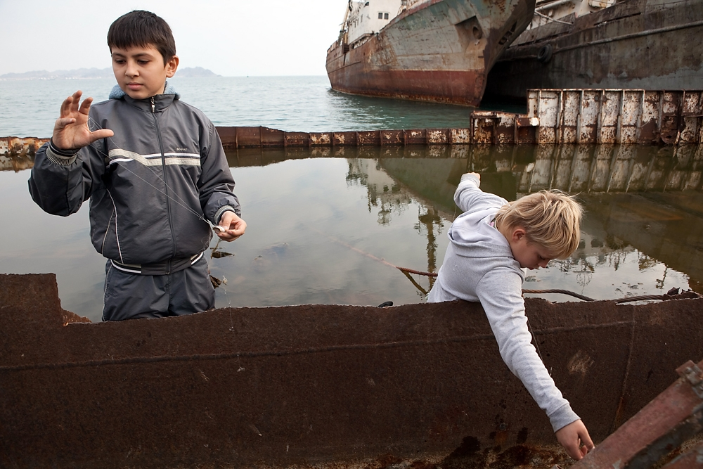 Boys fish from a rusty boat in the polluted harbor.