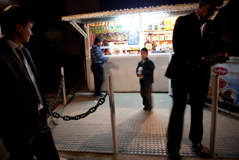 People shop at a kiosk in Turkmenbashi in the evening.