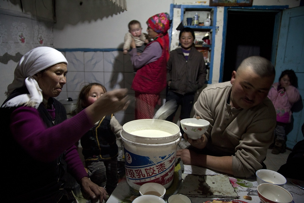 Orisbai Shatirbai's family eat yogurt after dinner in their home outside Tolbo, western Mongolia.