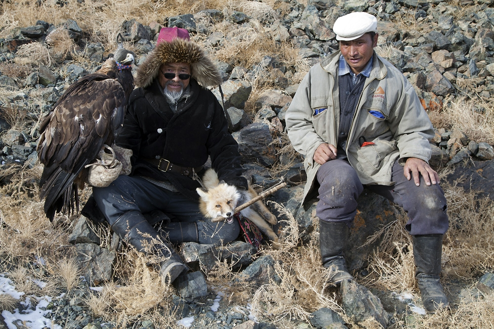 Shatirbai and his son Tuat sit with their golden eagle and the fox it caught outside Tolbo.