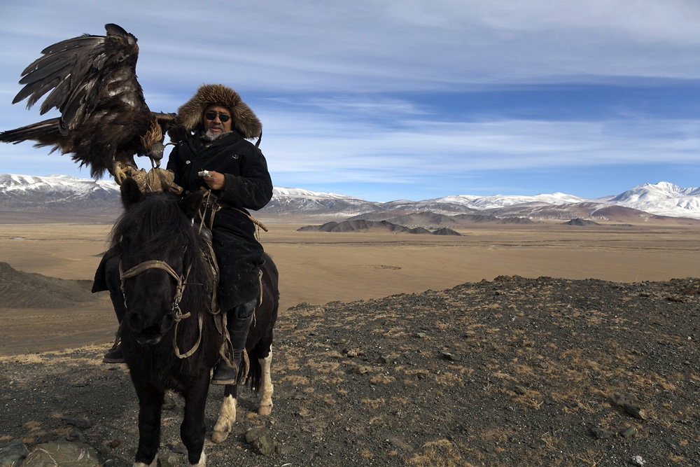 Shatirbai poses with a golden eagle just outside the western Mongolian town of Tolbo.