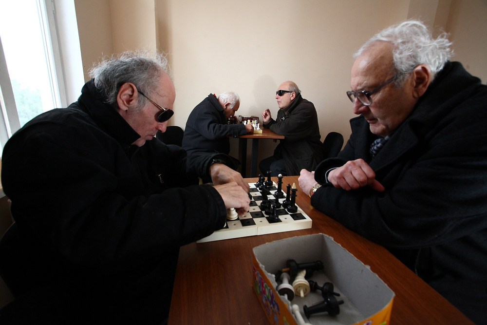 Partially blind instructor Nodar Gogadze (right) teaches chess club members of the Georgian Union for the Blind how to play.